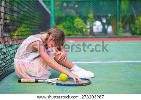 Little sad girl on tennis court - stock photo