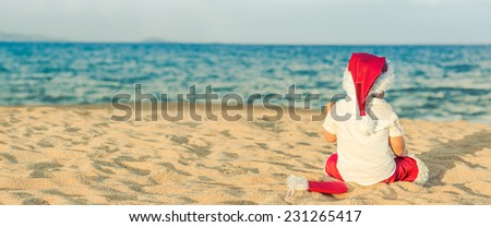 Little Santa on the beach. Panorama - stock photo