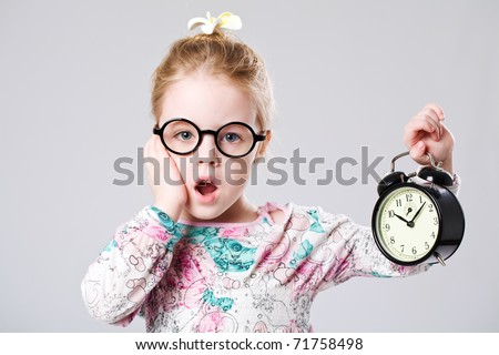 Little scary girl holding a clock - stock photo