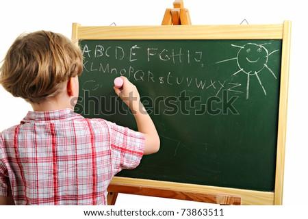 Little school boy writing on the blackboard - stock photo