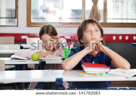 Little school girl writing notes with thoughtful boy in foreground at classroom - stock photo
