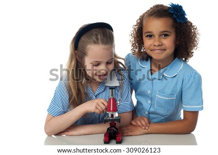Little school girls posing with a microscope - stock photo