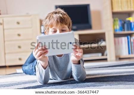 Little schoolboy having fun with his tablet in the living room - stock photo
