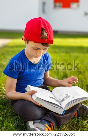 Little schoolboy sit and read book in park, outdoor portrait - stock photo