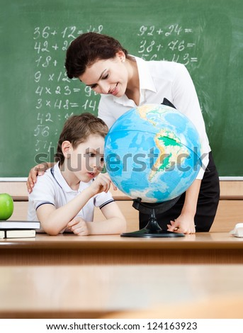Little schoolboy studies geography with terrestrial globe - stock photo