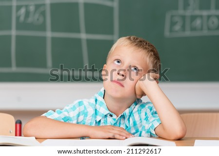 Little schoolboy without an answer staring up into the air hoping for inspiration as he sits at his desk in front of the blackboard - stock photo
