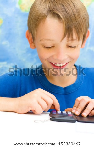 little schoolboy working for his maths subject with a calculator in front of world map - stock photo