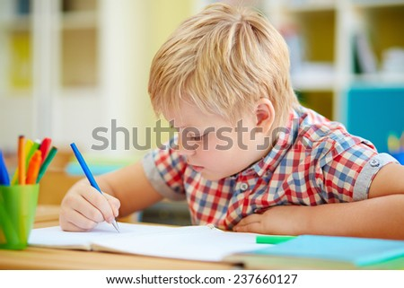 Little schoolboy writing in copybook at lesson - stock photo