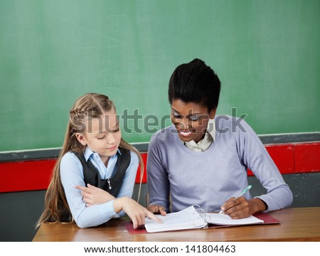 Little schoolgirl asking question to female teacher at desk in classroom - stock photo