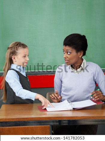 Little schoolgirl pointing in binder while teacher looking at her in classroom - stock photo