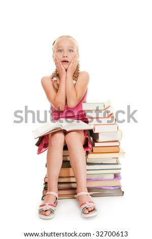 Little schoolgirl sitting on a stack of books - stock photo