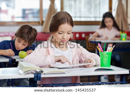 Little schoolgirl using digital tablet at desk with classmates studying in background - stock photo