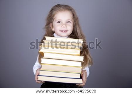Little schoolgirl with books. Studio shot. - stock photo