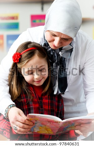 little schoolgirl with her young teacher in the classroom - stock photo