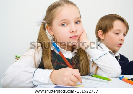 Little schoolgirl writing at school in workbook - stock photo