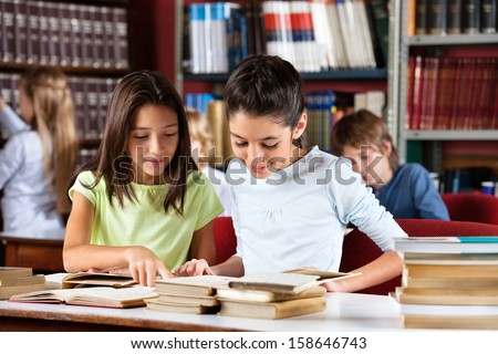 Little schoolgirls reading book together while sitting at table in library with classmates in background - stock photo