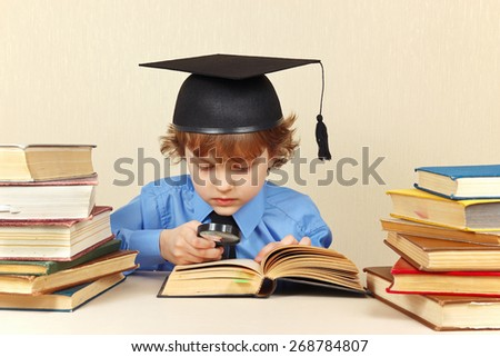 Little serious boy in academic hat reading an old books with a magnifying glass - stock photo