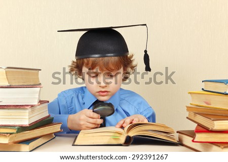 Little serious boy in academic hat studies an old books with a magnifying glass - stock photo