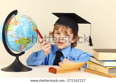 Little serious boy in academic hat with a pen showing on the geographical globe - stock photo