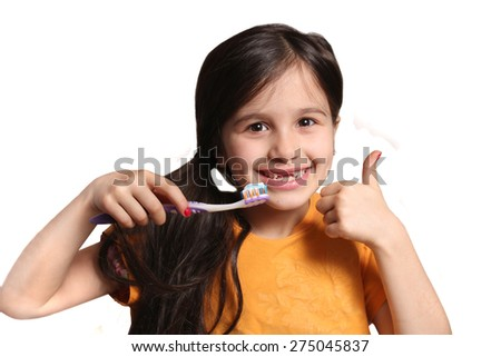 Little seven year old girl shows big smile showing missing top front teeth and holding a toothbrush with toothpaste and thumbs up on a white background - stock photo