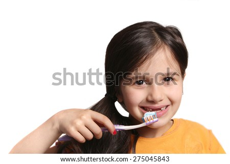 Little seven year old girl shows big smile showing missing top front teeth and holding a toothbrush with toothpaste on a white background - stock photo