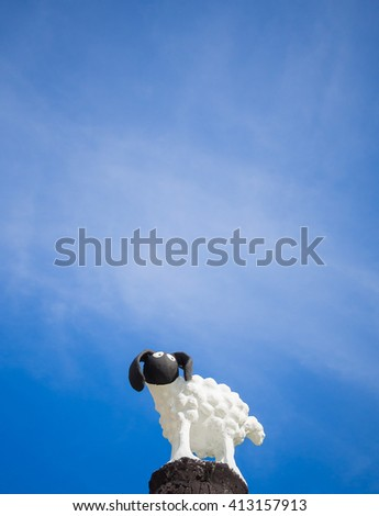 little sheep statue in blue sky background - stock photo