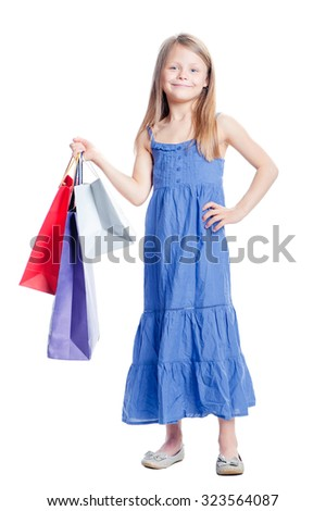 Little shopper. Full length of cute girl holding shopping bags. Isolated on white. - stock photo