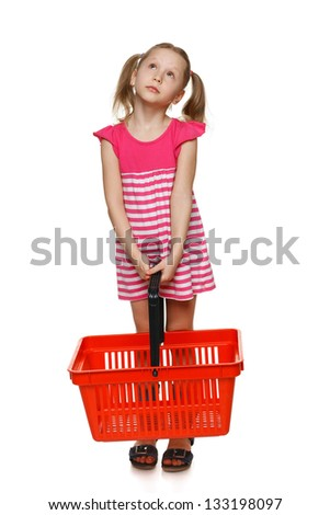 Little shopper. Little girl in full length holding empty shopping basket and looking up at blank space, over white background - stock photo