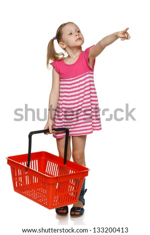 Little shopper. Little girl in full length holding empty shopping basket and pointing to the side, over white background - stock photo