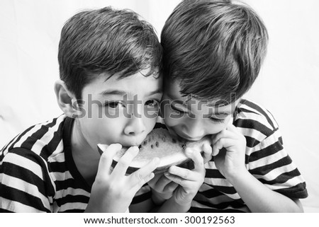 Little sibling boy eating watermelon together - stock photo