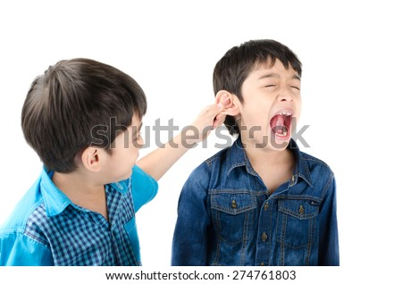 Little sibling boy fighting by pulling ear his brother on white background - stock photo