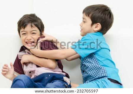 Little sibling boy  fighting on sofa - stock photo