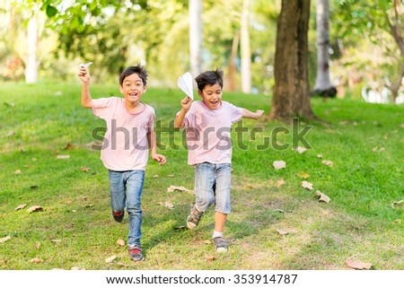 Little sibling boy playing plane paper in the park - stock photo