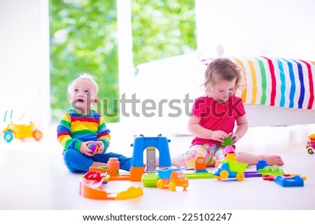 Little siblings playing with toy cars - stock photo