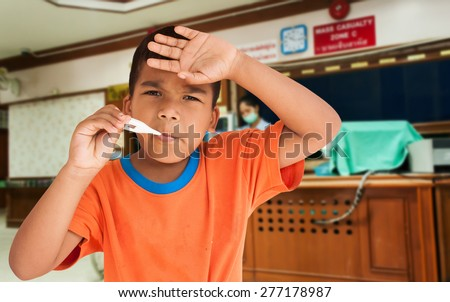 Little sick boy standing and holding  digital thermometer in mouth waiting doctor on hospital packground - stock photo