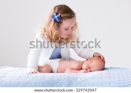 Little sister hugging her newborn brother. Toddler kid meeting new sibling. Cute girl and new born baby boy relax in a white bedroom. Family with children at home. Love, trust and tenderness concept.  - stock photo