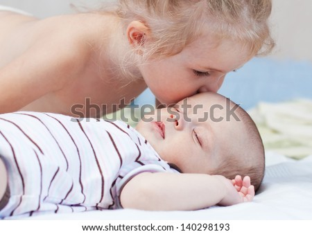 little sister kisses a sleeping newborn baby brother - stock photo