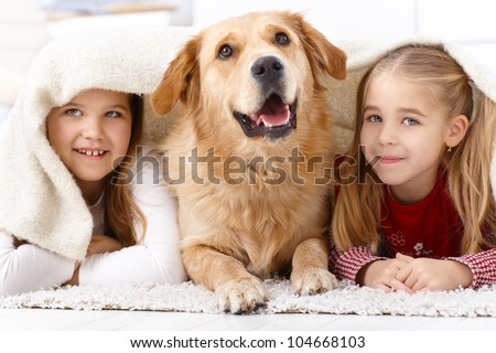Little sisters and pet dog having fun at home, lying prone on floor, smiling under blanket. - stock photo