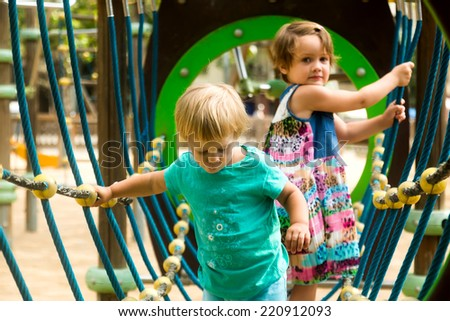 Little sisters having fun at action-oriented playground  - stock photo