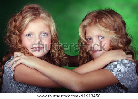 Little sisters hold each other - stock photo