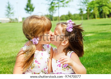Little sisters kissing each other - stock photo