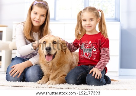 Little sisters kneeling on floor at home, fondling pet golden retriever, smiling. - stock photo