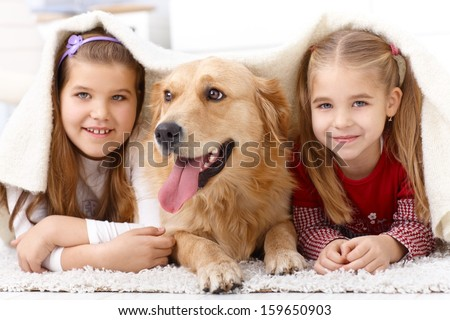 Little sisters lying on floor with dog, having fun under blanket, smiling. - stock photo