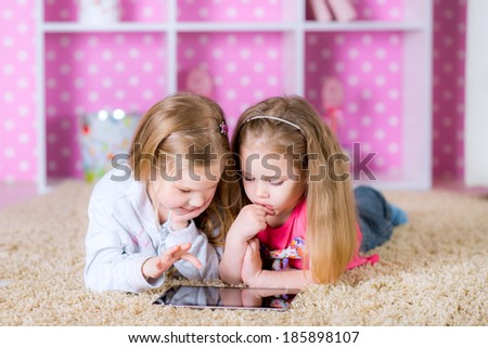 Little sisters playing on a tablet computing device - laying on the floor - stock photo