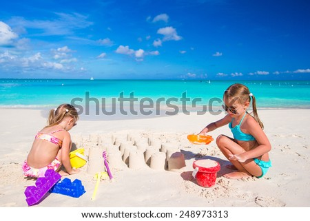 Little sisters playing with beach toys during tropical vacation - stock photo