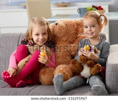 Little sisters smiling happily at home, sitting on sofa with big teddy bear. - stock photo