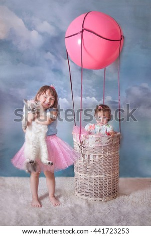 Little sisters with siberian cat in basket of balloon  on blue sky background - stock photo