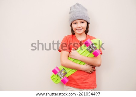 Little skater boy. Little boy in grey hat holding colorful skateboard and smiling while standing against grey background - stock photo