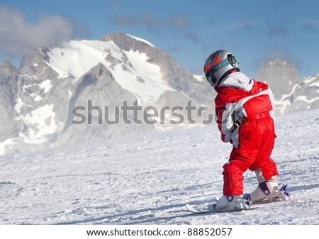 Little skier on a ski slope, Dolomite Mountains. - stock photo