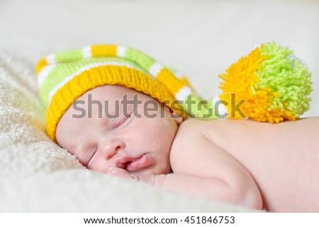 little sleeping newborn wearing a striped hat - stock photo